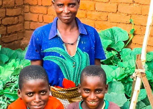 """Charity Cosmos can now pay the school fees for her sons by selling okra and papaya from her victory garden. """"My kids help me take care of the garden. They even enjoy cooking the vegetables!"""""""